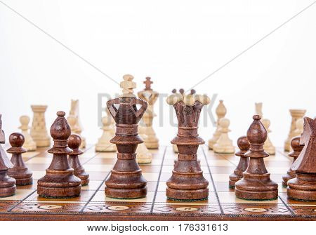 Wooden chess pieces on a chessboard with copy space above