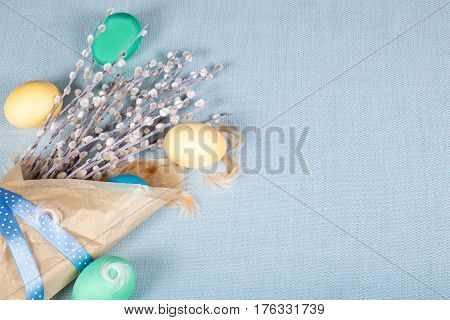 Paper package with willow painted eggs and feather on blue fabric tablecloth. Soft light and gentle easter background. Top view.