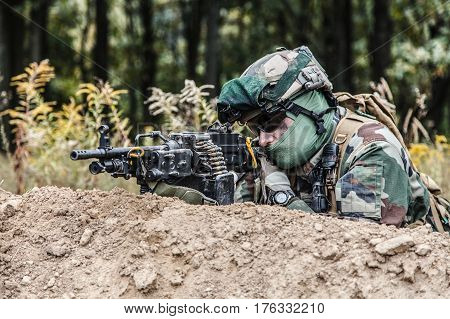Machine gunner of 1st Marine Infantry Parachute Regiment RPIMA firing from defensive position trench