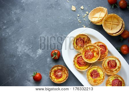 Cheese tomato tartlets puff pastry appetizers mini-pizzas with cheese and cherry tomatoes italian antipasti snack