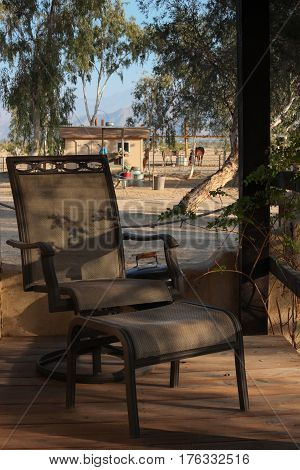 Empty lounge chair on porch at horse ranch in a desert in California, inviting viewer to sit in this peaceful, quiet place and relax.