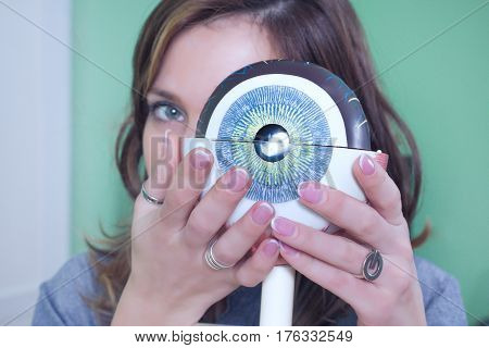 Ophthalmology oculus sample closeup. Ophthalmology, eye model close-up. The girl is holding a model of the eye.