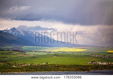 Town On The Lake Behind The Foothills. Spring Rain And Storm In Mountains