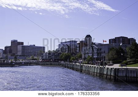 Wide view of the commerce and people milling about on the boardwalk at Halifax Harbor on a bright sunny day in September in Halifax, Nova Scotia