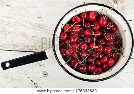 Red ripe juicy cherry in metal colander on white rustic wooden background. Sweet summer berries. Freshly harvested merry. Directly above. Top view. Copy space.