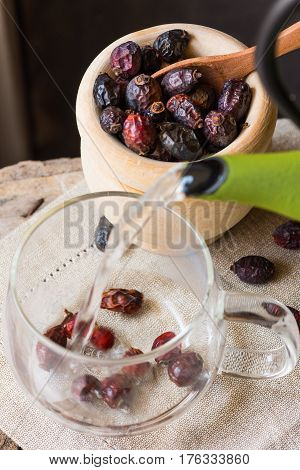Process of pouring hot water from pot brewing rose hip berries tea wood bowl linen towel cozy atmosphere kinfolk health concept