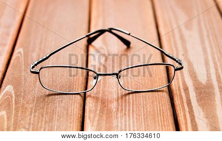 Glasses Concept. Glasses isolated on wood surface. Black glasses on wooden table. Glasses with dark metal rim. Office workplace with glasses. Old fashion glasses