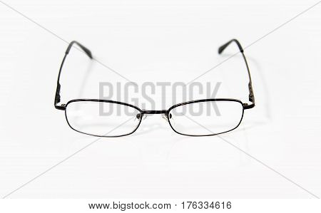 Glasses Concept. Glasses isolated on white surface. Black glasses on white table. Glasses with dark metal rim. Office workplace with glasses. Old fashion glasses