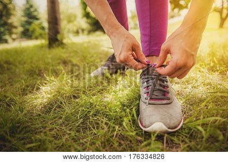 Running shoes being tied by women getting ready for jogging. focus on hands. Girl tying shoe laces