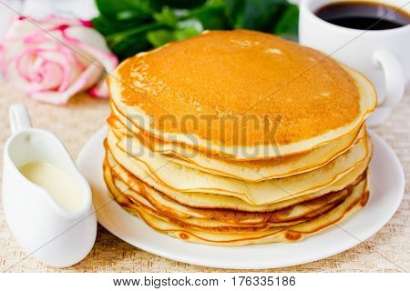 Stack of golden delicious pancakes coffee rose romantic breakfast on Valentine's Day and traditional food for Shrove Tuesday. American cuisine selective focus