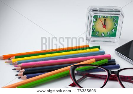 Many Colored Pencils, Clocks, Mobile Phone And Glasses