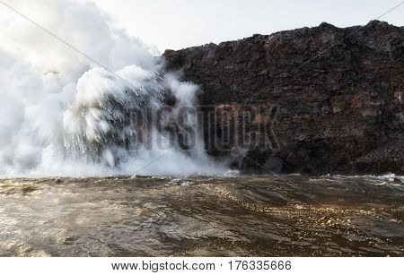 Large explosions occur as hot lava flows into cold sea water completely hiding the large fire hose molten lava flow.