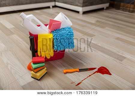 Crime cleaner concept. Bucket with sponges, chemicals bottles and plunger. Paper towel. Knife and splash of blood.
