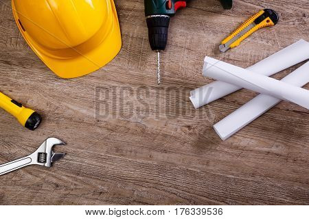 Yellow helmet, drill and flashlight. Construction concept. Adjustable wrench, architecture plans and knifes. Worker equipments on workplace.