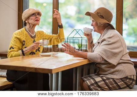 Two ladies at cafe table. Senior women are drinking coffee. The wise words.