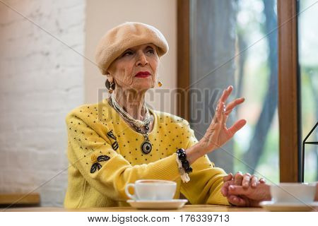Woman at table near window. Ladies holding hands. Calm down and listen.