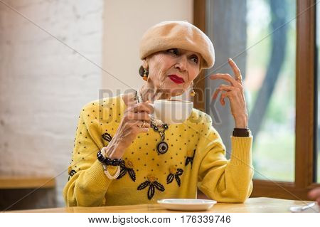 Old lady drinking coffee. Thoughtful woman at the table. Caffeine wakes my mind.