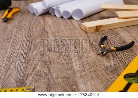 Paper knife, nippers and building level. Wooden planks and tape measure. Architecture plans. Wood rustic background.