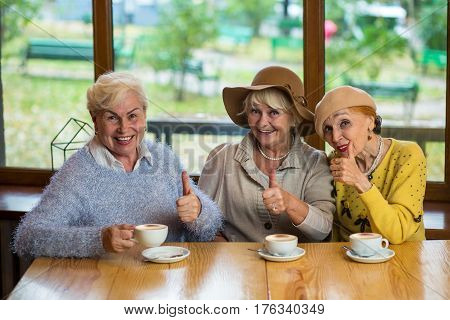 Senior ladies showing thumbs up. Three women and coffee cups. Everything is great.