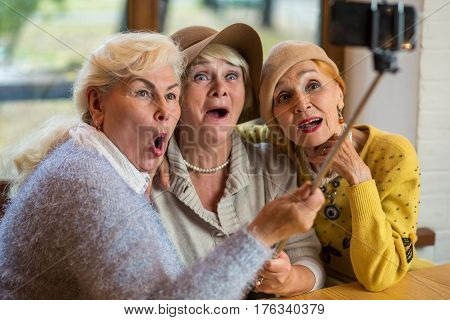 Women at table taking selfie. Senior ladies with surprised faces. Old friends get together.