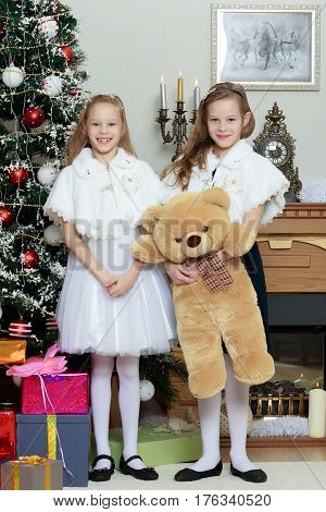 Cute little twin girls, sitting on the floor near the Christmas tree and electric fireplace on which candles are burning. In the hands of the girls boxes with gifts.