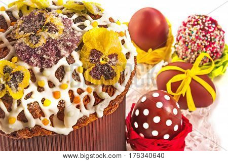 Typical home baked Easter cake covered with white icing sprinkled with color pops and candied flowers of viola tricolor and eggs on lace napkin. Horizontal top view close-up selective focus.