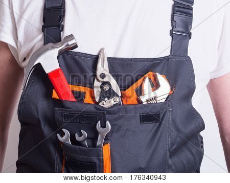 Photo of Worker in overalls with tools .