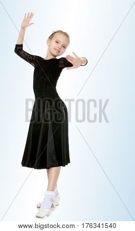 The slender little blonde girl dancer in the long dress of black color made specifically for performing .Girl graceful curves of the body.On the pale blue background.