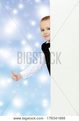 Cute little blonde boy in a black waistcoat and a white shirt and a bow at the neck , peeping over white banner.He holds up a thumb.Blue Christmas festive background with white snowflakes.
