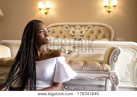 Girl with beautiful shiny dark skin sitting on the floor in front of big bed. Afroamericam woman with dreadlocks or african braids.
