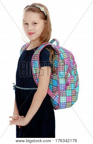Cute little girl with a school satchel behind shoulders. Girl stands sideways to the camera.Isolated on white background.