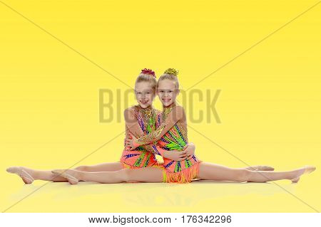 Two adorable little twin girls, gymnastics in the sports school. Girls beautiful gymnastic leotards. They do the splits.
