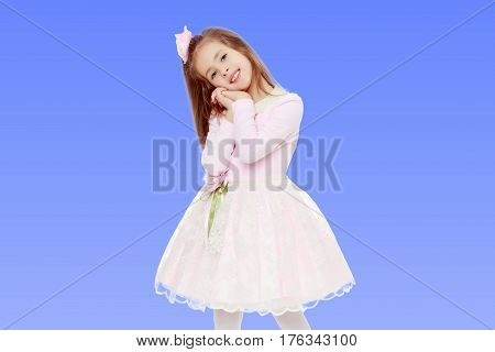 Dressy little girl long blonde hair, beautiful pink dress and a rose in her hair.She holds his palm near his face.On the pale blue background.