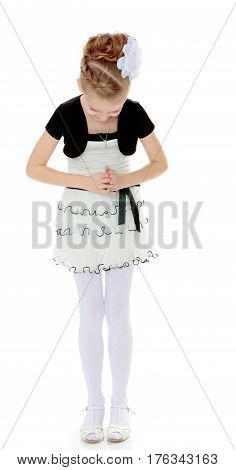 Beautiful little blonde girl dressed in a white short dress with black sleeves and a black belt.The girl leaned forward head. It is to bow.Isolated on white background.