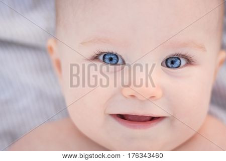Smiling baby girl with blue eyes closeup portrait