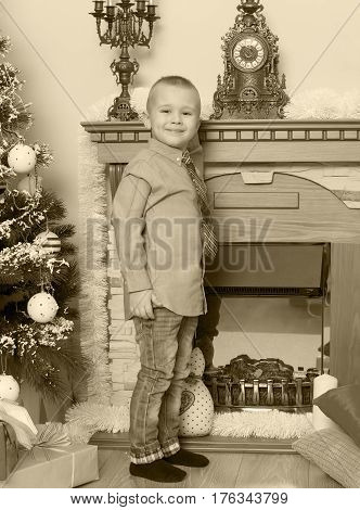 Elegant little boy by the fireplace in the Christmas night.Black-and-white photos , retro style.