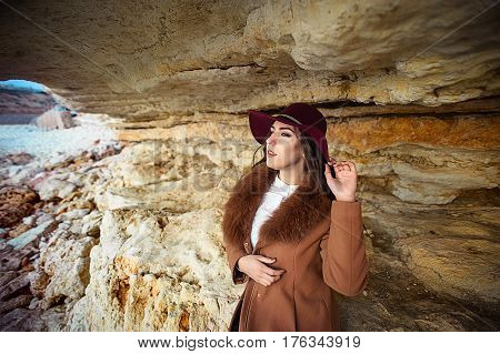 Beautiful girl in maroon felt hat close up portrait. Outdoor shoot.