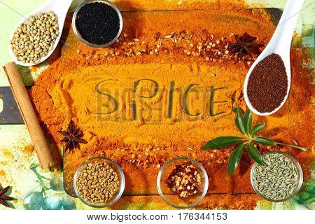 A board with turmeric and red chili powder with other spices like anise star methi seeds coriander seeds nigella seedss mustard seeds and fennel seeds top view.