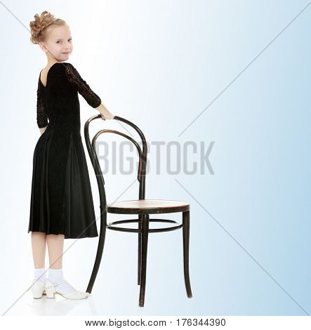 The slender little blonde girl dancer in the long dress of black color made specifically for performing .A girl stands in a half turn to the camera near the old Vienna chair.On the pale blue background.