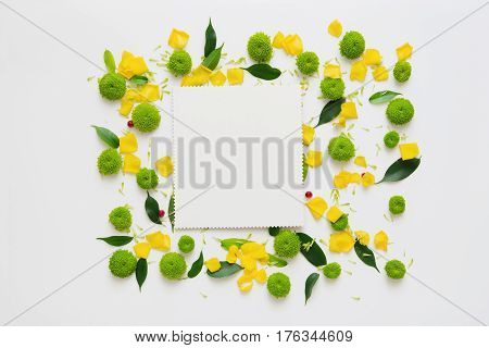Paper with wreath frame from roses and chrysanthemum flowers, ficus leaves and ripe rowan on white background. Overhead view. Flat lay.