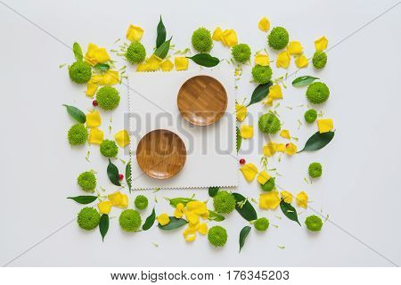 Sheet of paper and wooden plates with pattern from petals of chrysanthemum flowers, ficus leaves and ripe rowan on white background. Overhead view. Flat lay.