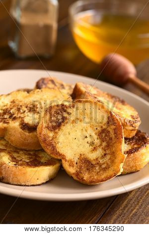 French toast made of baguette honey and cinnamon powder in the back photographed with natural light (Selective Focus Focus on the upper part of the standing toast)
