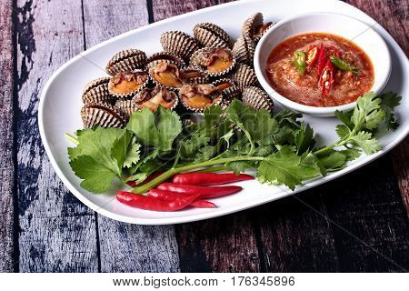 Fresh and delicious soft-boiled blood cockles shell topped red chili coriander and Chinese celery served with spicy sauce in Korea pattern black dish