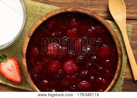 German Rote Gruetze (red groats) red berry pudding made of strawberry blueberry raspberry and redcurrants cooked with sugar and starch served with glass of milk photographed overhead on wood with natural light