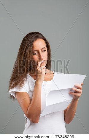 Thoughtful Young Woman Reading A Document
