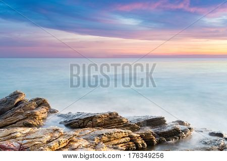 beautiful seascape of reef with sunset glow over the sea long exposure time