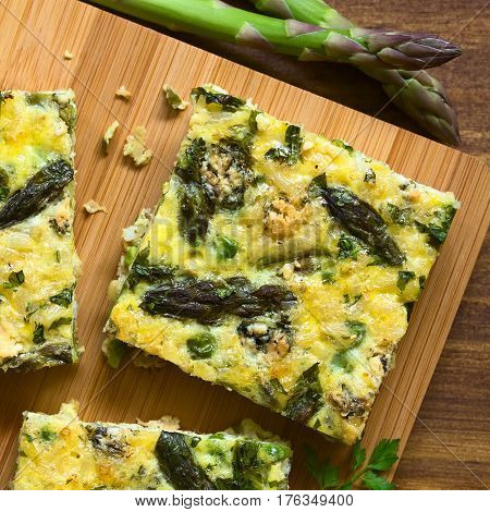 Frittata made of eggs green asparagus pea blue cheese parsley and brown rice photographed overhead on wooden board with natural light