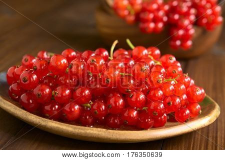Raw red currants (lat. Ribes rubrum) on plate photographed on dark wood with natural light (Selective Focus Focus one third into the redcurrants)