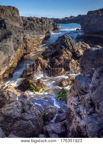 Lava rock off stunning glass beach near Port Allen town on Kauai Hawaii.