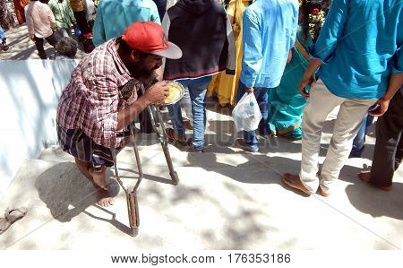 KEESARAGUTTA,HYDERABAD,INDIA;FEBRUARY 24:-Indian physically challenged man eats food begging on stairs to temple on Mahasivaratri,on February 24,2017 in Hyderabad,India